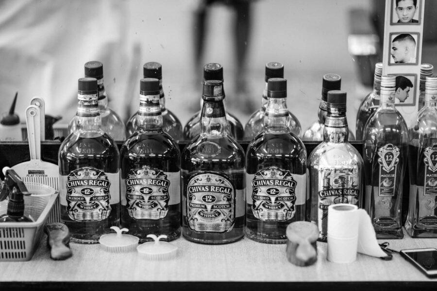 Barber shop display bottles of Chivas Regal Scotch Whisky Little India, Brickfields, Kuala Lumpur – Malaysia