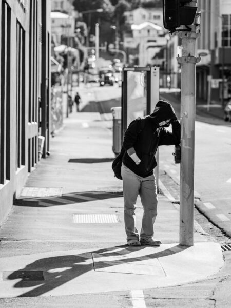 Man standing at a pedestrian crossing leaning against the traffic light. Black and white street photo Wellington - New Zealand
